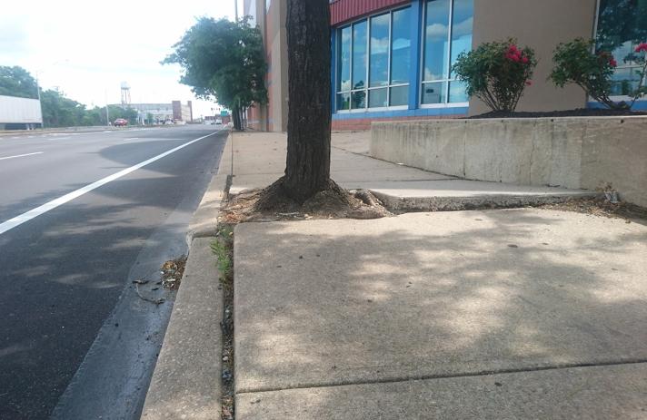 newly paved street with adjacent broken sidewalk,